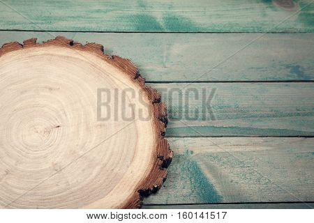 Round wooden board on old blue wooden table.
