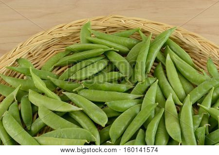 Close up of Green snap beans in wood basket in preparation for removing strings