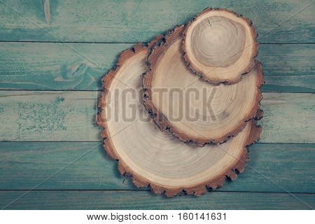 Round three wooden boards on old blue wooden table.