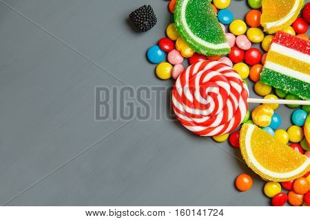 Colorful Candies And Lollipops Over Gray Background. Top View With Copy Space