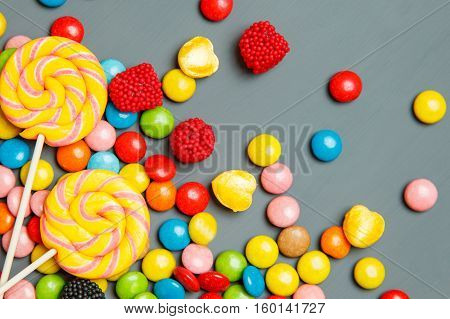 Colorful candies on wooden background. top view