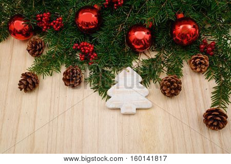 Fir tree with christmas decorations on the wooden background
