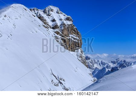 Summit of Mt. Titlis in the Swiss Alps on a windy day in winter. Mount Titlis is a mountain of the Uri Alps, located on the border between the Swiss cantons of Obwalden and Bern.