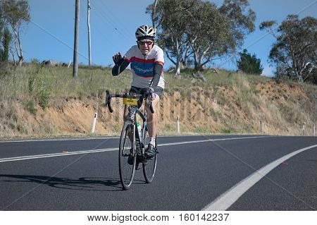 Jindabyne, Snowy Mountains Region, Australia - December 3, 2016: The first L'Etape cycling event held in Australia (by Le Tour de France).  Cyclist smiles and waves were common in the 2nd race stage.