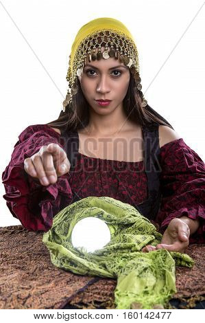 Female psychic or fortune teller pointing finger forward at the viewer. She has a crystal ball and isolated on a white background