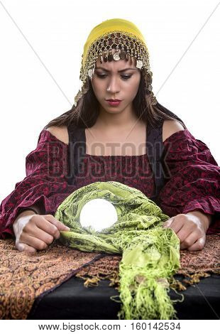 Female fortune teller or psychic is concerned or depressed about a vision of the future seen in her crystal ball