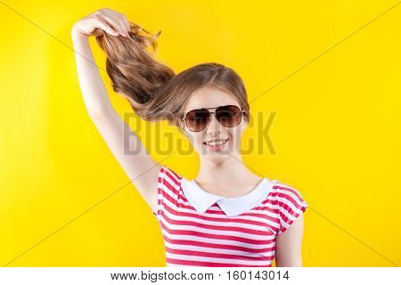 Pretty Girl In Sunglasses Posing On A Yellow Background. Bright Stock Photos. Positive Human Emotion