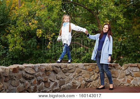 Mother and daughter in autumn park. Mom helping her daughter to go on the stone fence. Family time.