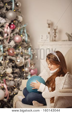 Little girl holding a large Christmas ball. In the background is a Christmas tree and 25 December. The festive mood. Waiting for the holiday.