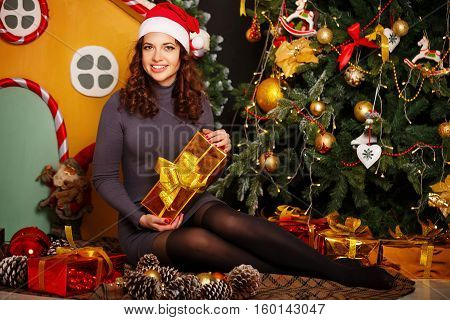 Girl in Santa hat holding a Christmas gift and sitting at the Christmas tree. Merry Christmas.