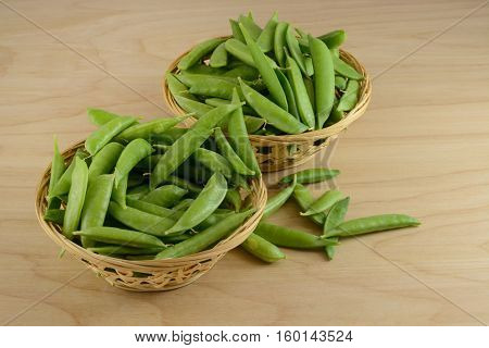 Green snap beans in wood baskets in preparation for removing strings