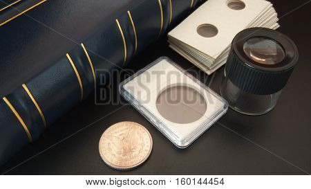 Old American silver dollar on black table with magnifying glass, numismatic supplies and album for coins - Numismatic scene