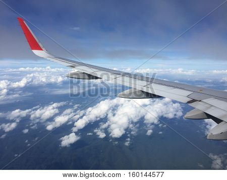 View of clouds from the airplane.Aerial view of cloud and blue sky with wing's airplane.Traveling and journey concept.