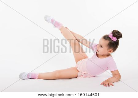 Little Girl Performing An Exercise Sitting On The Floor. Pretty Funny Gymnast In A Pink Dress On A L