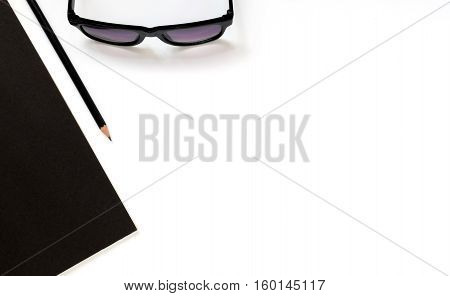 Flat lay photo of office desk with balck book sun glasses and pencil with copy space background
