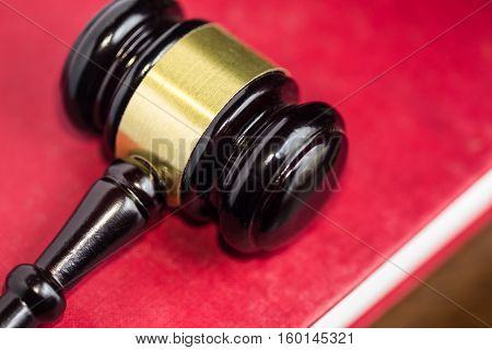 Gavel on red cover legal textbook (Concept of justice)