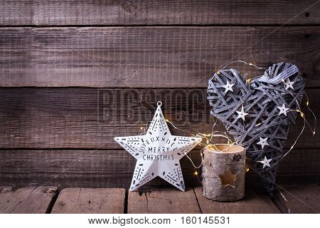 Christmas star decorative heart candleholder and fairy light on aged wooden background. Decorative christmas composition. Place for text.
