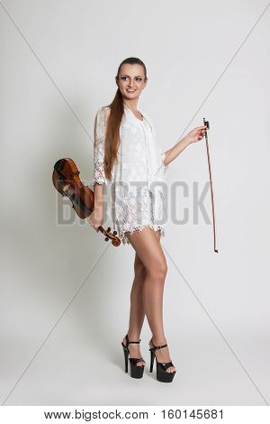 Beautiful Young Woman In A White Dress With A Violin In His Hands.