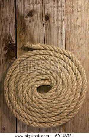 Hempen rope is coiled on an old wooden background