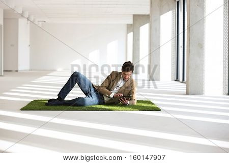 Full length of young businessman using digital tablet while reclining on turf in office