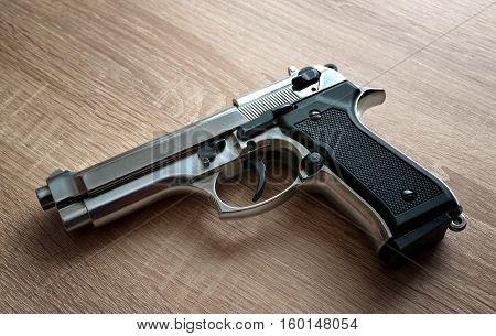 Silver steel pistol on a wooden board.