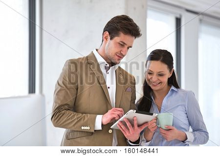 Businesswoman with male colleague using tablet computer in office