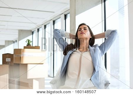 Relaxed young businesswoman with hands behind head in new office