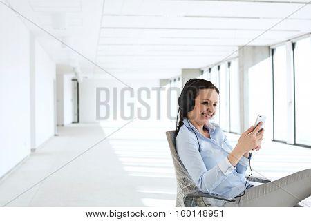 Smiling businesswoman listening music through headphones in empty office