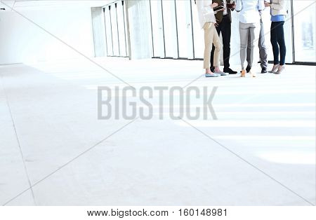 Low section of business people standing together in empty office