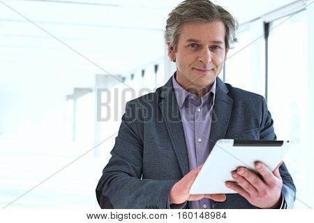 Portrait of mature businessman using digital tablet in new office