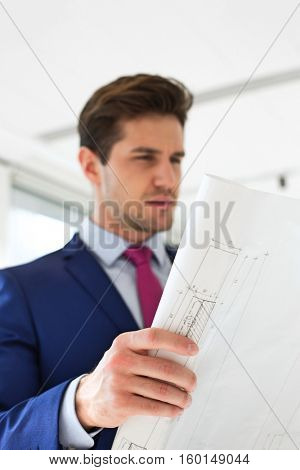 Confident young businessman analyzing blueprint in new office