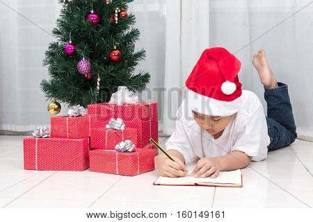 Asian Chinese Little Boy Writting Book Beside Christmas Presents