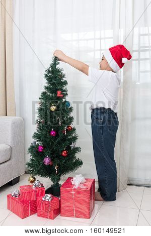 Asian Chinese Little Boy Decorating Christmas Tree At Home