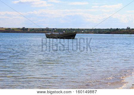 Old fishing boat at anchor in sea near sand shore