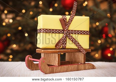 Wrapped Gift On Wooden Sled And Christmas Tree With Lights In Background
