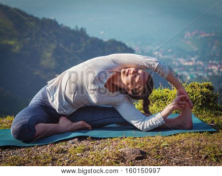 Yoga outdoors - young sporty fit woman doing Hatha Yoga asana parivritta janu sirsasana - Revolved Head-to-Knee Pose - in mountains in the morning. Vintage retro effect filtered hipster style image.
