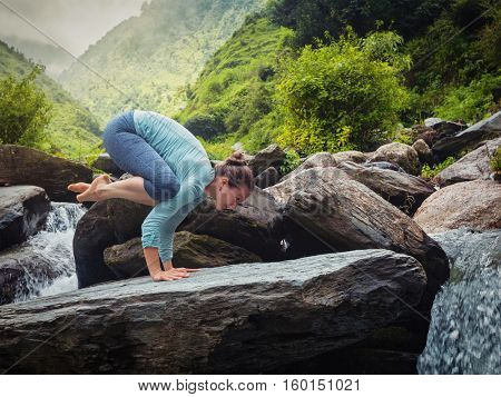 Woman doing Bakasana asana crane pose arm balance outdoors at waterfall. Vintage retro effect filtered hipster style image.