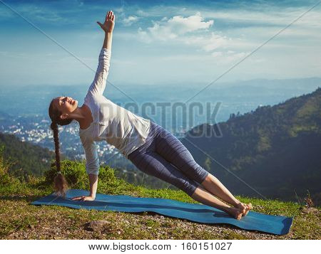 Yoga outdoors - beautiful sporty fit woman doing yoga asana Vasisthasana - side plank pose in mountains. Vintage retro effect filtered hipster style image.