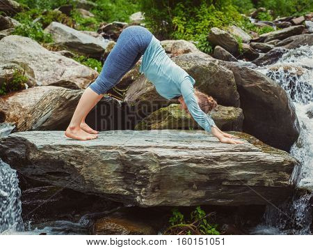 Young sporty fit woman doing yoga asana Adho mukha svanasana - downward facing dog - at tropical waterfall. Vintage retro effect filtered hipster style image.
