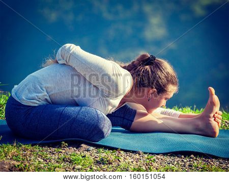 Woman doing Ashtanga Vinyasa yoga asana Ardha baddha padma paschimottanasana half bound lotus intense west stretch pose outdoors in mountains in the morning. Vintage retro filtered hipster style imag