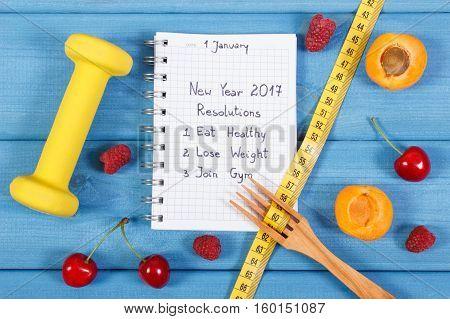 New Year Resolutions Written In Notebook On Blue Board