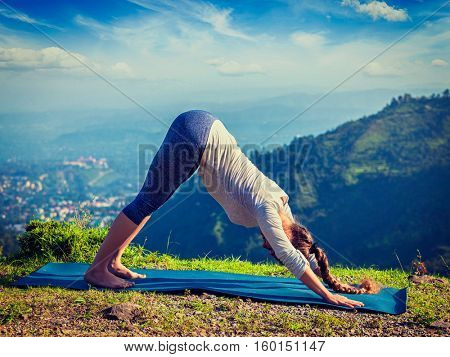 Yoga outdoors - woman doing Ashtanga Vinyasa Yoga asana Adho mukha svanasana downward facing dog in Surya Namaskar Sun Salutation outdoors in Himalayas in morning. Vintage retro hipster style image.