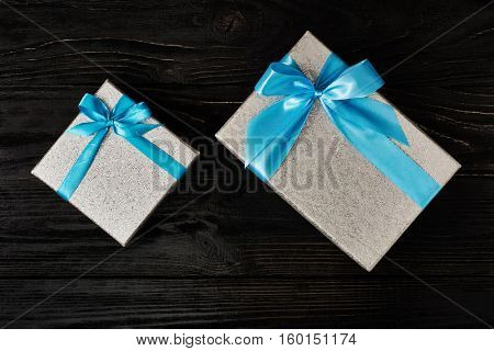 Gift birthday Christmas present concept - silver gift box with blue ribbon on dark wooden background