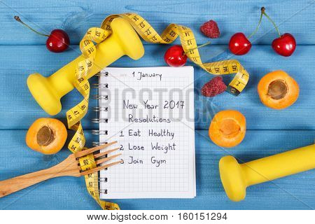 New Year Resolutions Written In Notebook On Blue Board