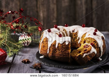 Christmas homemade cake with nuts, apples and cranberries with icing on dark wooden background. Selective focus