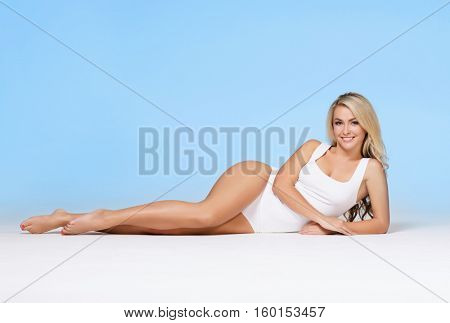 Fit and sporty girl posing over cyan background. Sport, fitness, diet, weight loss and healthcare concept.