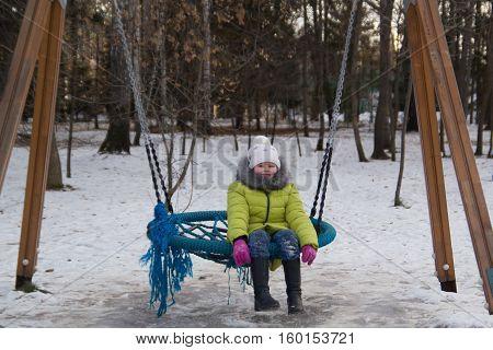 Happy child: little girl on the children's rocker at winter city park, horizontal