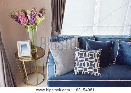 Navy Blue Modern Classic Sofa And Retro, Gray And Blue Pillows With A Lovely Orchid Vase On Side Tab