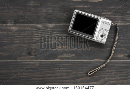 back silver digital compact camera with blank black screen display and hand strap on black vintage wood table top view with copy space included clipping path for compact camera black screen display