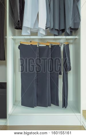 Men slacks hanging in white wardrobe at home
